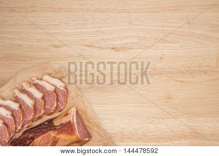 Smoked meat on a wooden table. Top view.