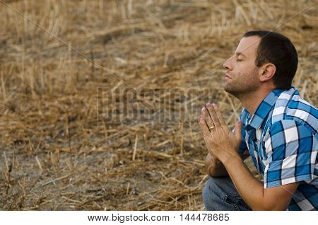 Young man in a plaid shirt praying crouched down in an outdoor field.