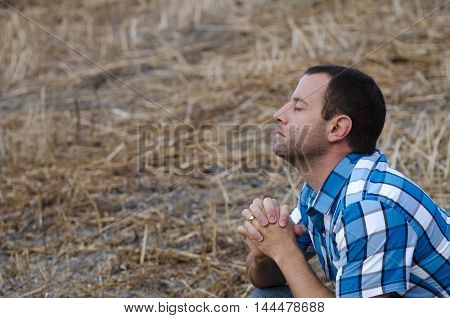 Man crouching down and praying with his hands clasped on a hillside wearing a plaid shirt.