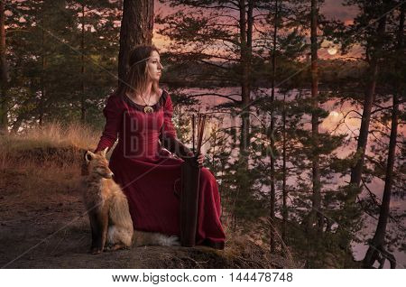 A young woman in medieval clothes with a bow and arrow sitting beside the river with a Fox against the setting sun