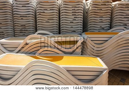 Close up of sunbeds on the beach stacked, ready to be put on the beach to enjoy the tourists of the sun and good weather. Summer holiday