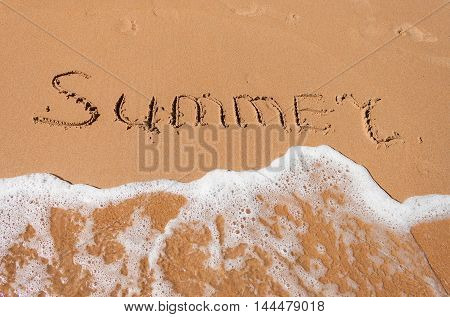 The word summer written in the sand on a beach and sea in background