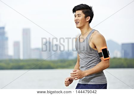 young asian male jogger with fitness tracker attached to arm running with skyline in the background.