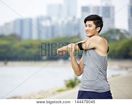young asian male jogger with fitness tracker attached to arm warming up by stretching arms and upper body before running city skyline in the background.