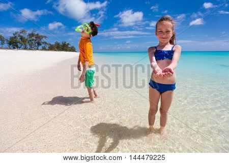 Kids having fun at tropical beach during tropical summer vacation playing together at shallow water