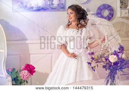 Pretty adult woman wearing vintage beautiful white dress and umbrella standing in bright retro room