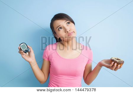 asian woman hold a blood glucose meter and a donut