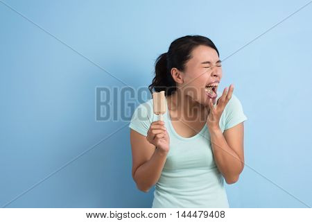 Asian young woman with hypersensitive teeth eating ice lolly, closeup portrait with copyspace