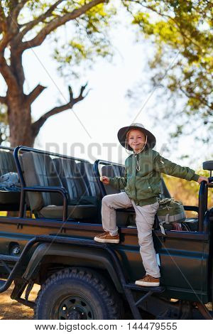 Adorable little girl in South Africa safari on morning game drive near open vehicle