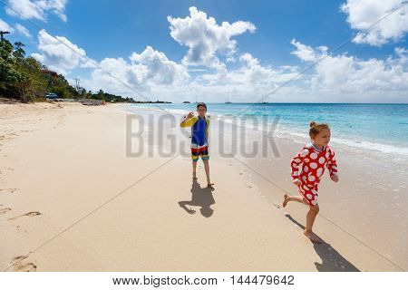 Kids brother and sister at tropical beach during Caribbean summer vacation