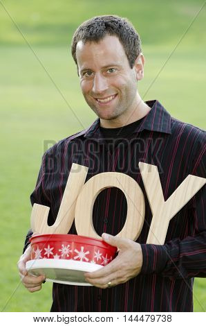Man holding a Holiday themed plastic container and wooden letters that spell the word