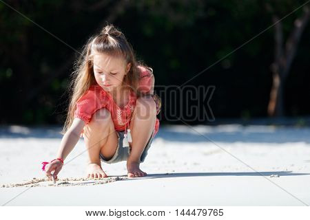 Little girl at tropical beach playing with sand