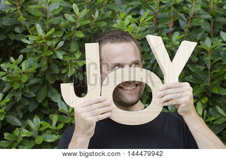 Man hiding behind the wooden letters of the word joy.