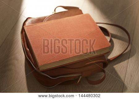 Book with handbag on wooden background