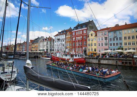 COPENHAGEN DENMARK - AUGUST 15 2016: Boats in the docks Nyhavn people restaurants and colorful architecture. Nyhavn a 17th century harbour in Copenhagen Denmark on August 15 2016.