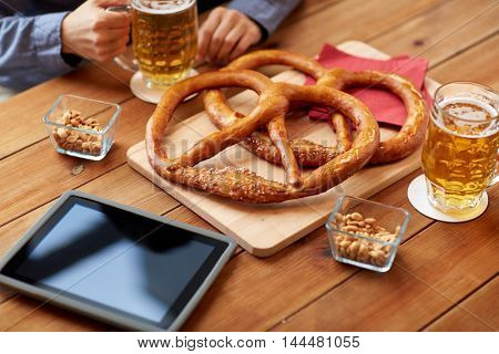 people, leisure, technology and drinks concept - close up of man drinking beer with pretzels, peanuts and tablet pc computer on table at bar or pub