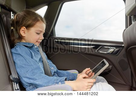 transport, road trip, travel, technology and people concept - happy little girl with tablet pc driving in car safety seat
