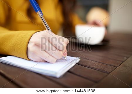 leisure and people concept - close up of young woman drinking cocoa and writing to notebook at city street cafe