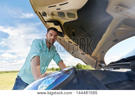 road trip, transport, travel and people concept - young man with open hood of broken car at countryside