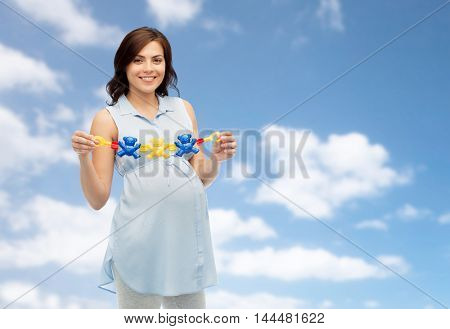 pregnancy, motherhood, people and expectation concept - happy pregnant woman holding rattle toy over blue sky and clouds background
