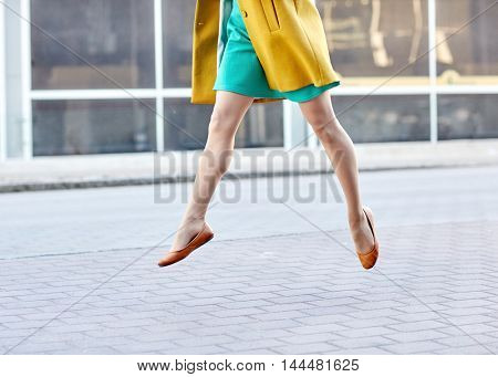 fashion and people concept - happy young woman or teenage girl legs flying above pavement on city street