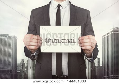 Junkmail on paper what businessman is holding on cityscape background