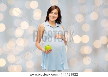pregnancy, healthy eating, food and people concept - happy pregnant woman holding green apple over holidays lights background