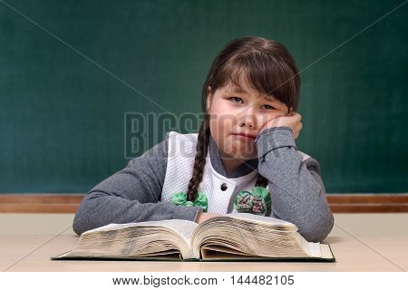 Girl in the classroom. Great tutorial blackboard. Child obesity full. The schoolgirl is upset crying and does not want to learn. Portrait