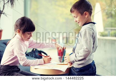 childhood, leisure, friendship and people concept - happy little girl and boy drawing and coloring picture with pencils at home