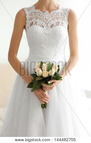 Bride in beautiful dress holding wedding bouquet