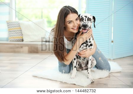 Owner with her dalmatian dog  on a carpet