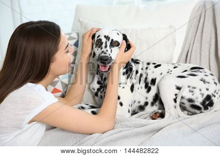 Owner with her dalmatian dog sitting on a couch