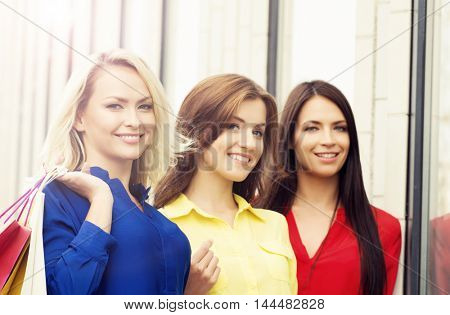 Pretty women with a shopping bags. Friends walking outdoor in a city. Discount, shopping and money spending concept.