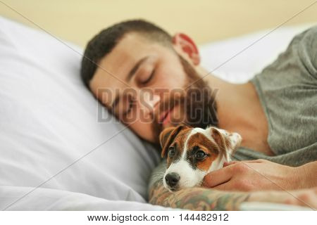 Handsome man with cute dog sleeping in bed