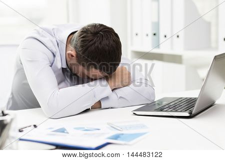 business, people, fail, paperwork and technology concept - businessman with laptop computer and papers working in office