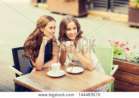 people, communication and friendship concept - smiling young women drinking coffee and talking at outdoor cafe