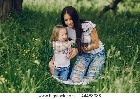 girl with her mom on  picnic at the tree in summer