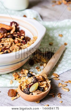 Homemade granola with oatmeal, dried cranberry, almond, walnut, pumpkin seeds in a bowl, selective focus