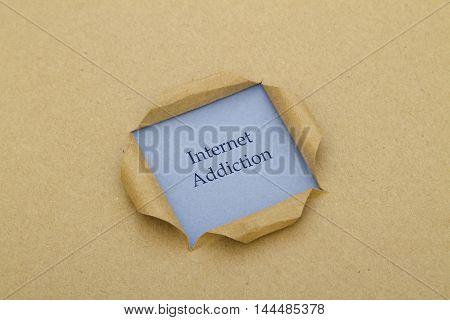 Internet Addiction written under torn paper .