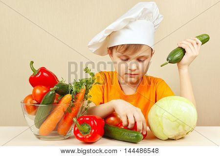 Little boy in chefs hat with vegetables at the table