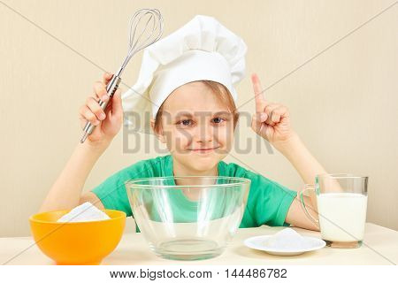 Young smiling chef at the table with ingredients is going to cook a cake