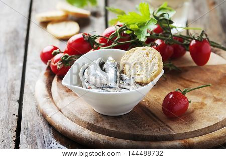 Italian traditional anchovy with bread and tomato selective focus