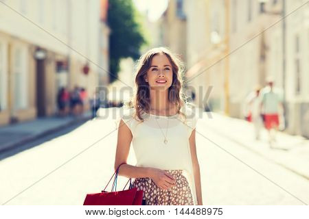 sale, consumerism and people concept - happy young woman with shopping bags walking along city street