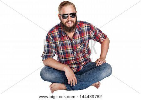young bearded lumberjack sitting in sunglasses, studio isolated