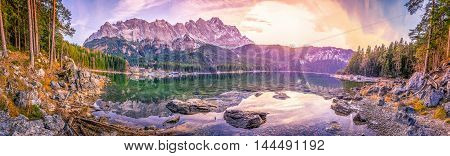 Alps mountains reflected in a lake at sunset - Panoramic view with the bavarian Alps mountains mirrored in the water of the Eibsee lake located in Grainau Germany at dusk.