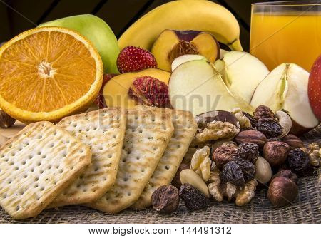 Breakfast with fruits and nuts - Food photography with a delicious and nutritious meal formed of fresh fruits a mix of nuts salty crackers and a glass of orange juice.