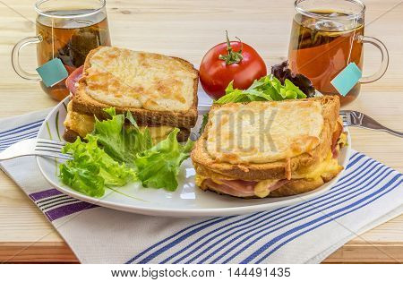 Cheese sandwiches and tee for two people - Appetizing food image with gratin cheese sandwiches, fresh salad and warm cups of tea, enough for two people.