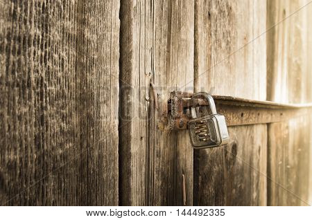 Metal lock on old barn - Close up with a metal lock on the door of an old wooden barn