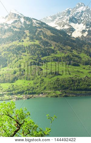 Mountain and lake in the morning landscape - Landscape with the morning sun illuminating softly the lake Walensee and the snowy Swiss mountain peaks. Image taken from the village Quentin Switzerland.