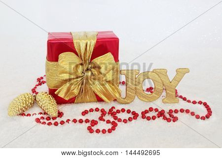 Christmas gift box with gold bow, glitter joy sign, pine cone baubles and red bead decorations on snow background.